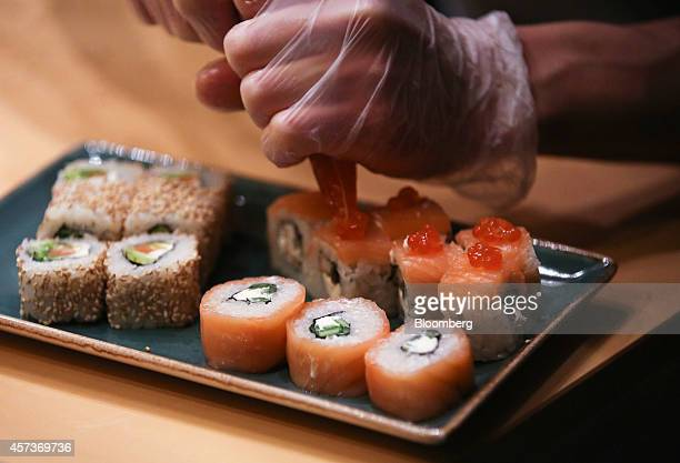 A chef applies the final touches onto a salmonbased sushi dish as he prepares a customers order in the kitchen at a Planeta Sushi restaurant operated...
