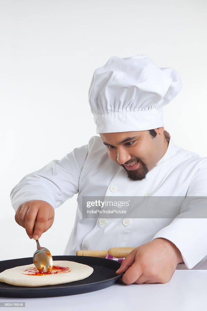Chef applying topping on pizza dough : Stock Photo