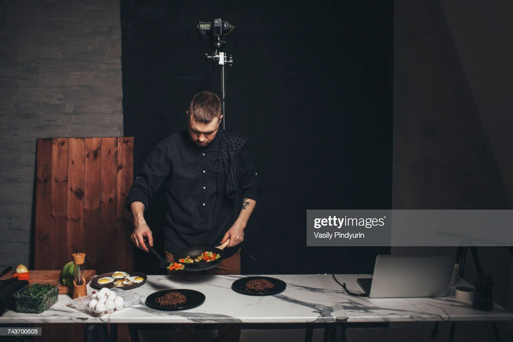 Chef arranging food on marble counter against backdrop at studio : Stock Photo