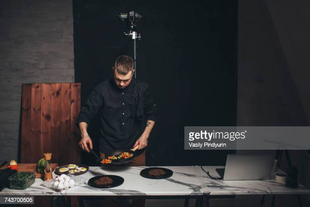 Chef arranging food on marble counter against backdrop at studio