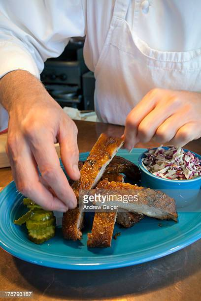 Chef arranging ribs on blue plate.