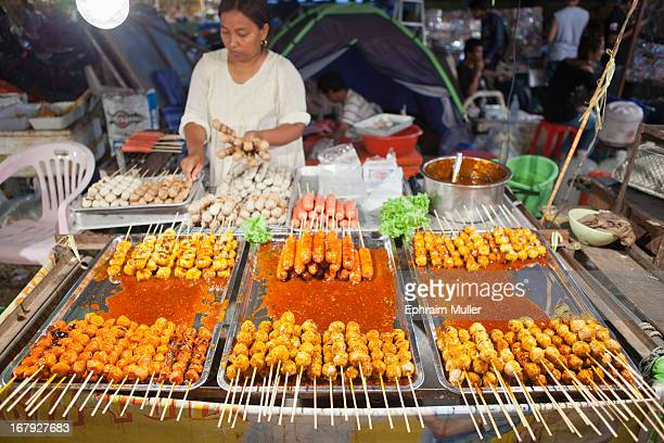 Chef at a night market in Koh Samui Thailand displays a selection of kebabs doused in sauce