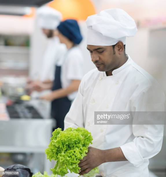 Chef at his restaurant checking the lettuce before making a salad