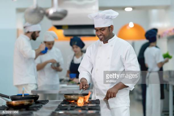 Chef at his restaurant using a frying pan to flambe a meat looking very happy