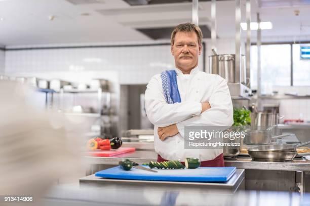 Ein Koch in seiner Küche schaut fokussiert und streng in die Kamera