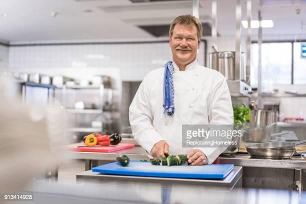 Ein Koch in seiner Küche  währrend er Essen zubereitet und in die Kamera lächelt