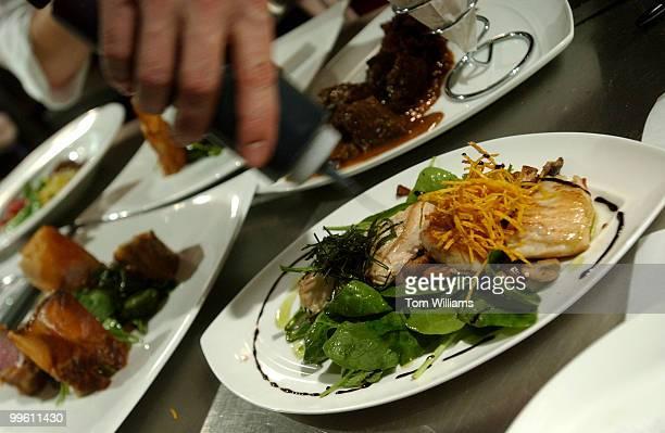 Chef Bart Vandaele garnishes a seabass dish at Belga Cafe on 8th St SE