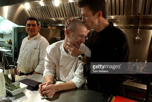 Chef Bart Vandaele kisses cook Benjamin Clerici at Belga Cafe on 8th St SE Cook Christian Villalta looks on