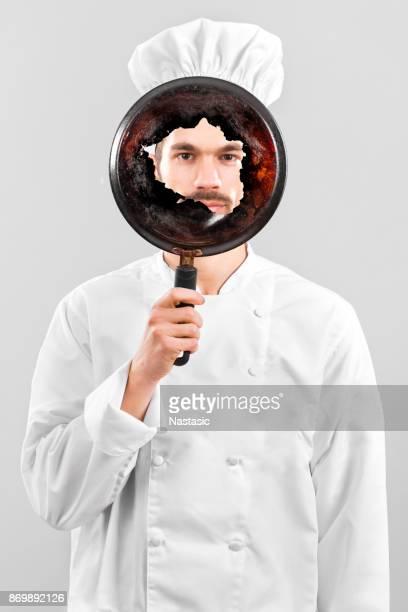 Koch hinter verbrannten Topf