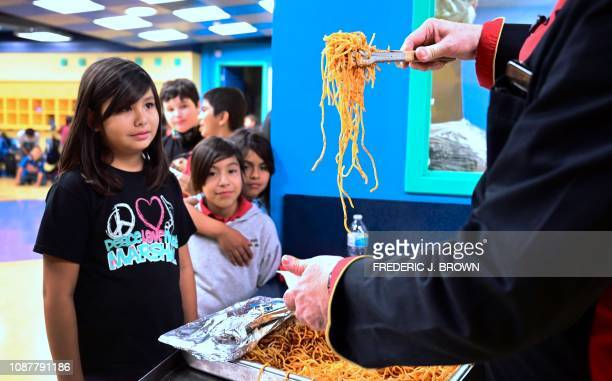 Chef Bruno Serato serves spaghetti to children some of whom come from homeless backgrounds at an afterschool Boys and Girls Club program in Anaheim...