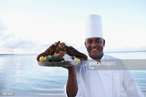 Chef Carrying Lobster Dish at Beach