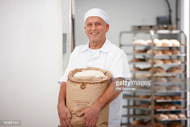 Chef carrying sack of flour in kitchen
