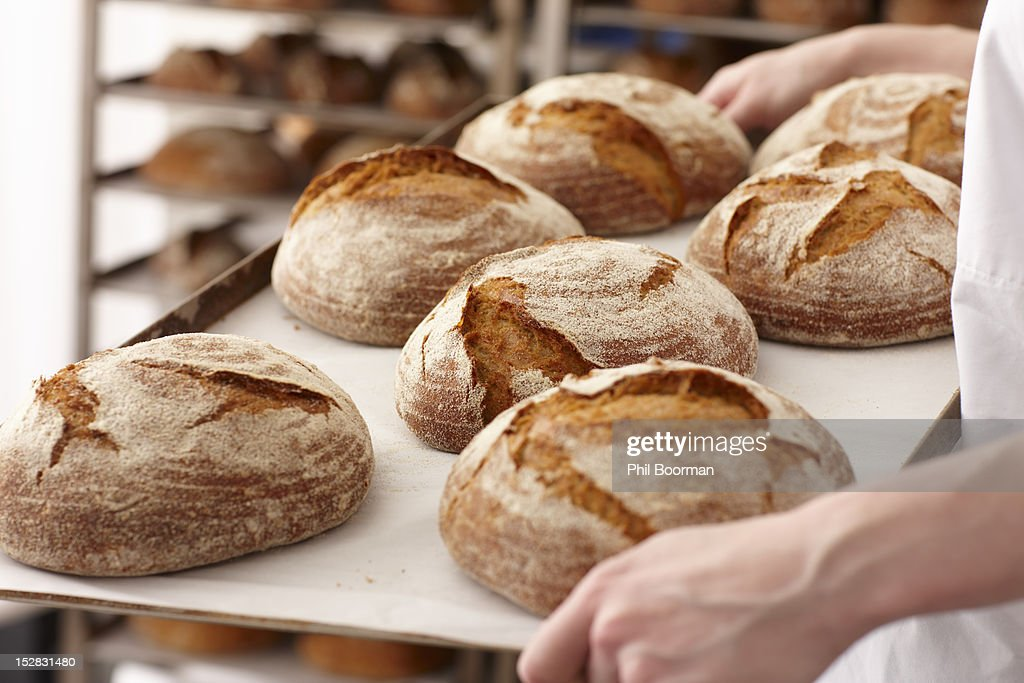 Chef carrying tray of bread in kitchen : Stock-Foto