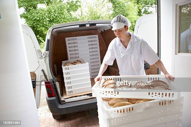 Chef carrying trays of bread to van