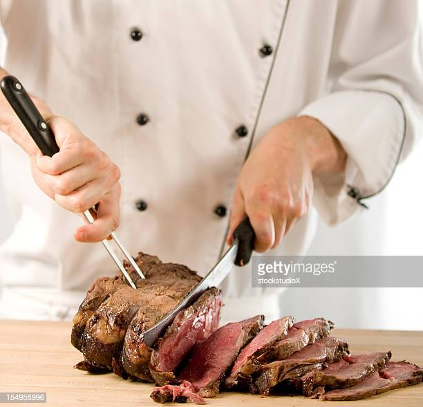 Chef carving perfectly cooked prime rib roast beef
