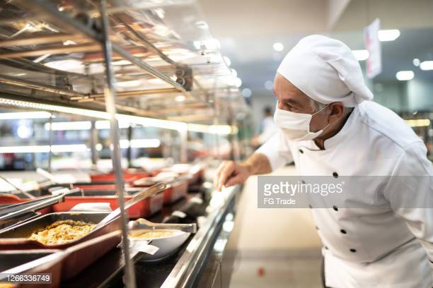 chef checking food on the buffet - cafeteria stock pictures, royalty-free photos & images