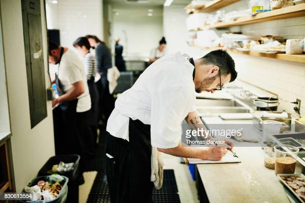 Chef checking list in restaurant kitchen while preparing for dinner service