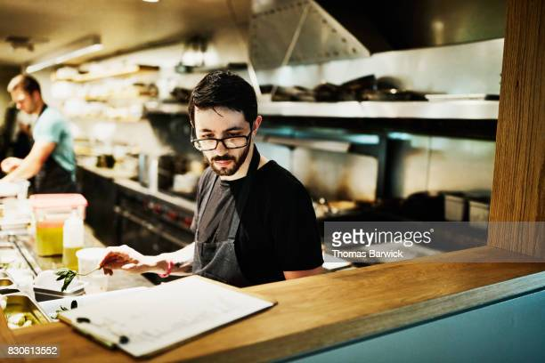 Chef checking list while preparing for dinner in restaurant kitchen