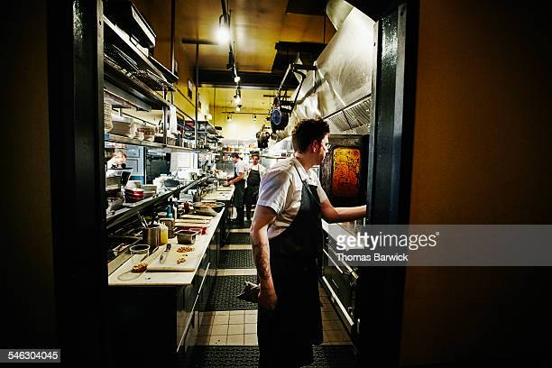 Chef checking on food being prepared in oven