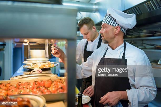chef checking order in traditional italian restaurant kitchen - オトレイ ストックフォトと画像