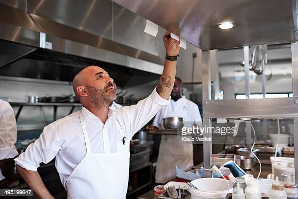 chef checking orders in the kitchen at restaurant - bucht stock-fotos und bilder