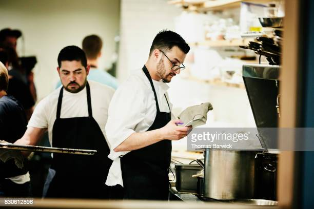 Chef checking smartphone while working in restaurant kitchen