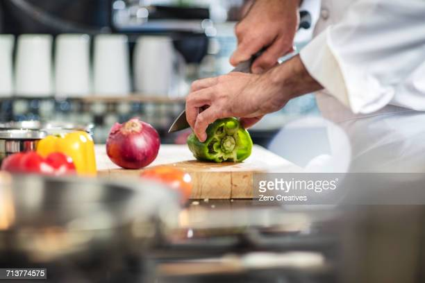 chef chopping green pepper on chopping board - green bell pepper stock pictures, royalty-free photos & images