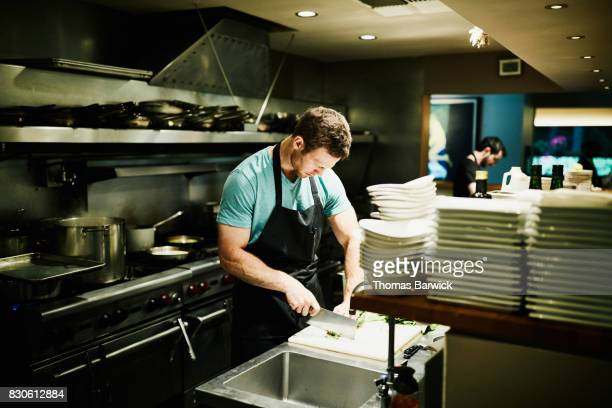 Chef chopping onions while preparing for dinner service in restaurant