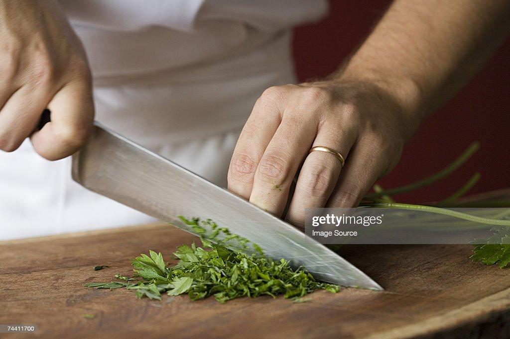 Chef chopping parsley : Stock Photo