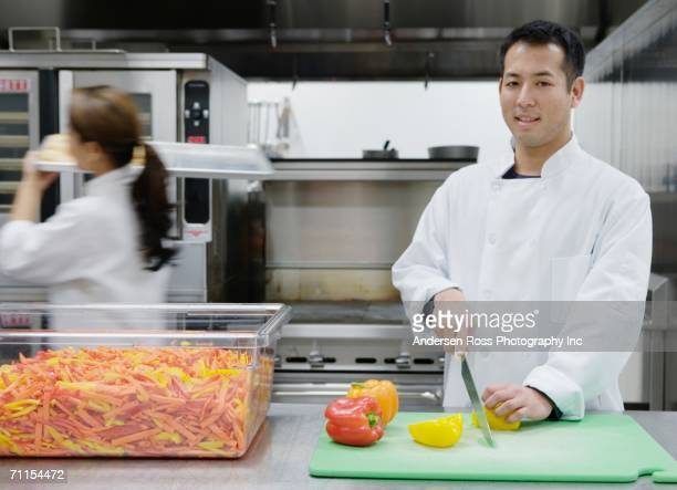 Chef chopping vegetables in kitchen