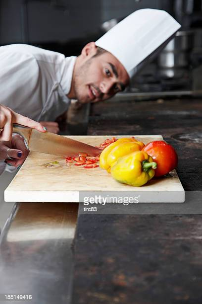 Chef closely watching another chopping a pepper