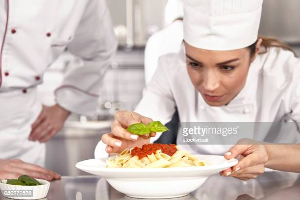 Chef completing pasta with tomato