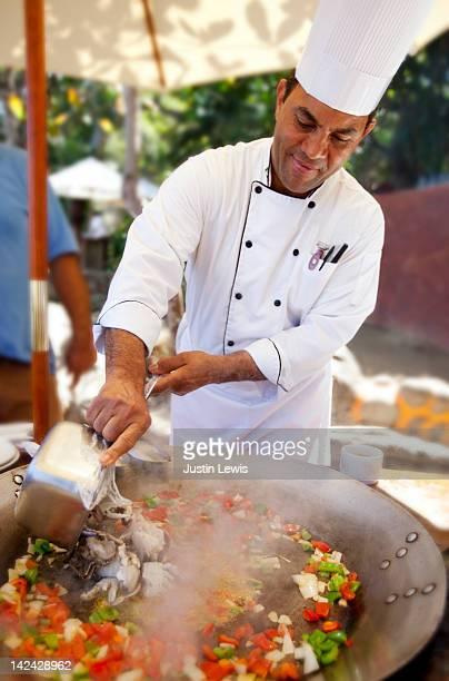 Chef cooking a big bowl of sea food paiya