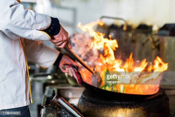 chef cooking with flame in a frying pan on a kitchen stove - chinese food stock pictures, royalty-free photos & images
