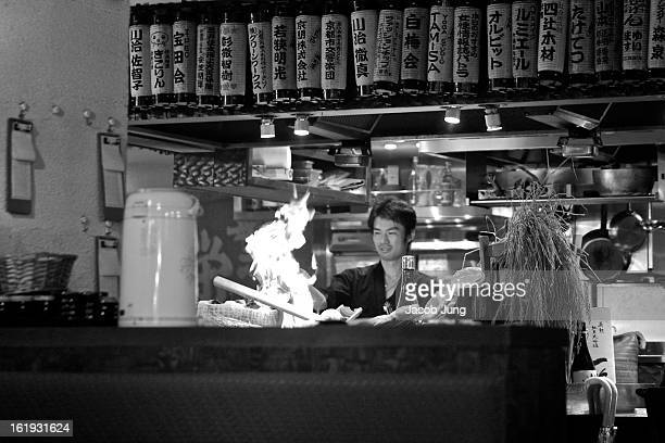 CONTENT] A chef cooks as a large flame rises over the grill in an izakaya ie Japanesestyle eatery / drinking establishment in central Kyoto Nakagyo...