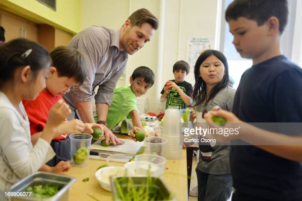 Chef Cory Vitiello from the Harbord Room Restaurant helps kids from Dovercourt Public School prepare the ingredients for what will become braised...