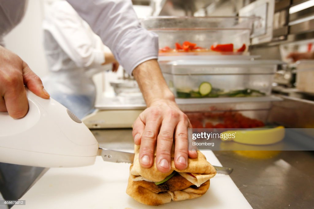 A chef cuts a freshly made sandwich wrap in the kitchen of a branch of food retailer Pret a Manger Ltd. in London, U.K., on Monday, March 27, 2017. Food chain Pret a Manger said it's concerned about Brexit because just one in 50 applicants seeking jobs is British. Photographer: Luke MacGregor/Bloomberg via Getty Images