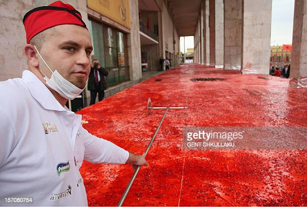 A chef cuts a huge cake with the Albanian flag symbols measuring 550 meters square on the main boulevard of Tirana on November 28 2012 Albania marks...