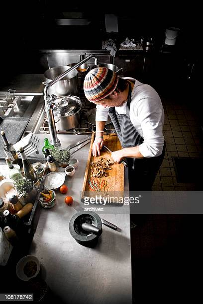 Chef Cutting Figs on Wooden Chopping Board in Restaurant Kitchen