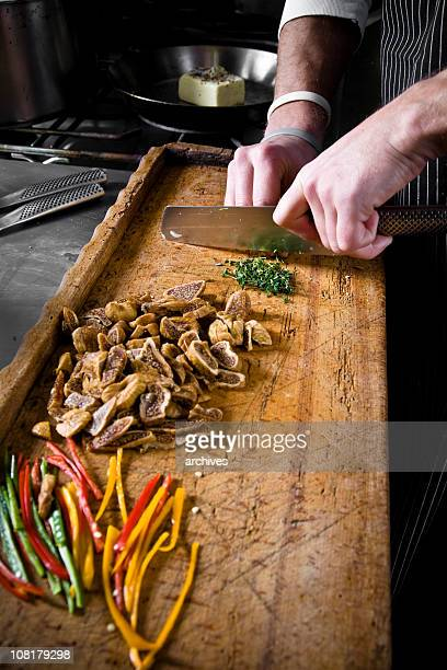 Chef Cutting Herbs on Wooden Chopping Board in Restaurant Kitchen