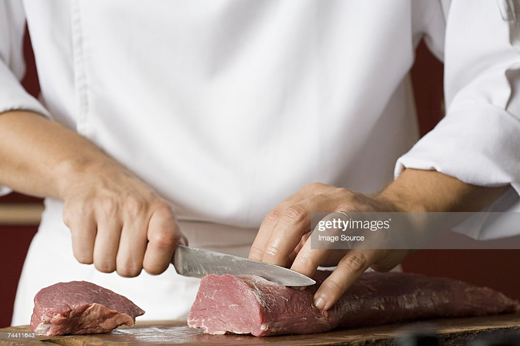 Chef cutting meat : Stock Photo