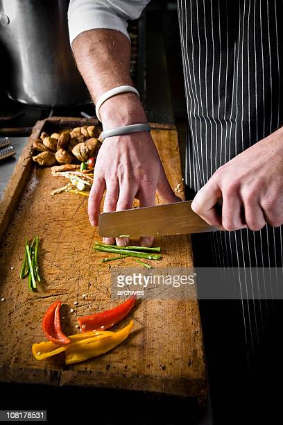 Chef Cutting Peppers on Wood Board with Large Cooking Knife