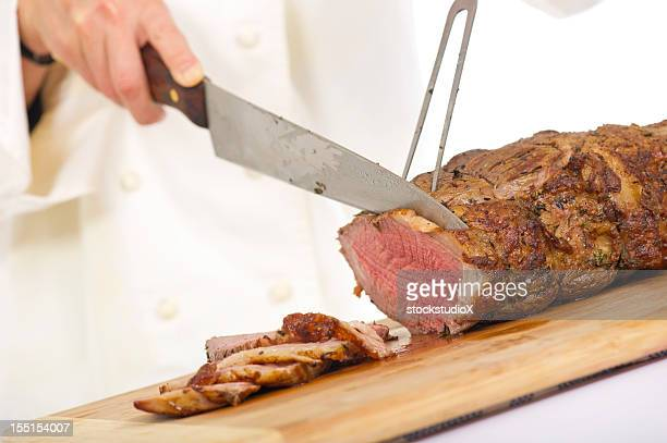 Chef cutting slices from a piece of roast beef