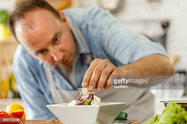 Chef decorating a plate with healthy salad