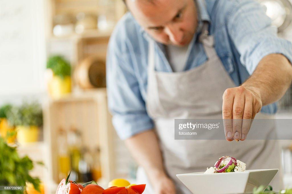 Lo Chef decorare un piatto con insalata sano : Foto stock