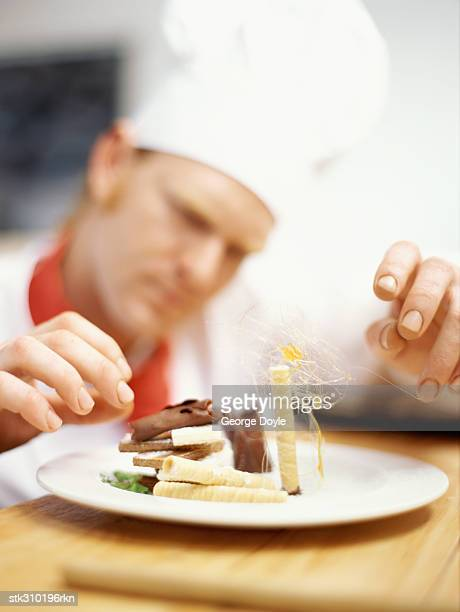 chef decorating a plate with wafers and chocolate