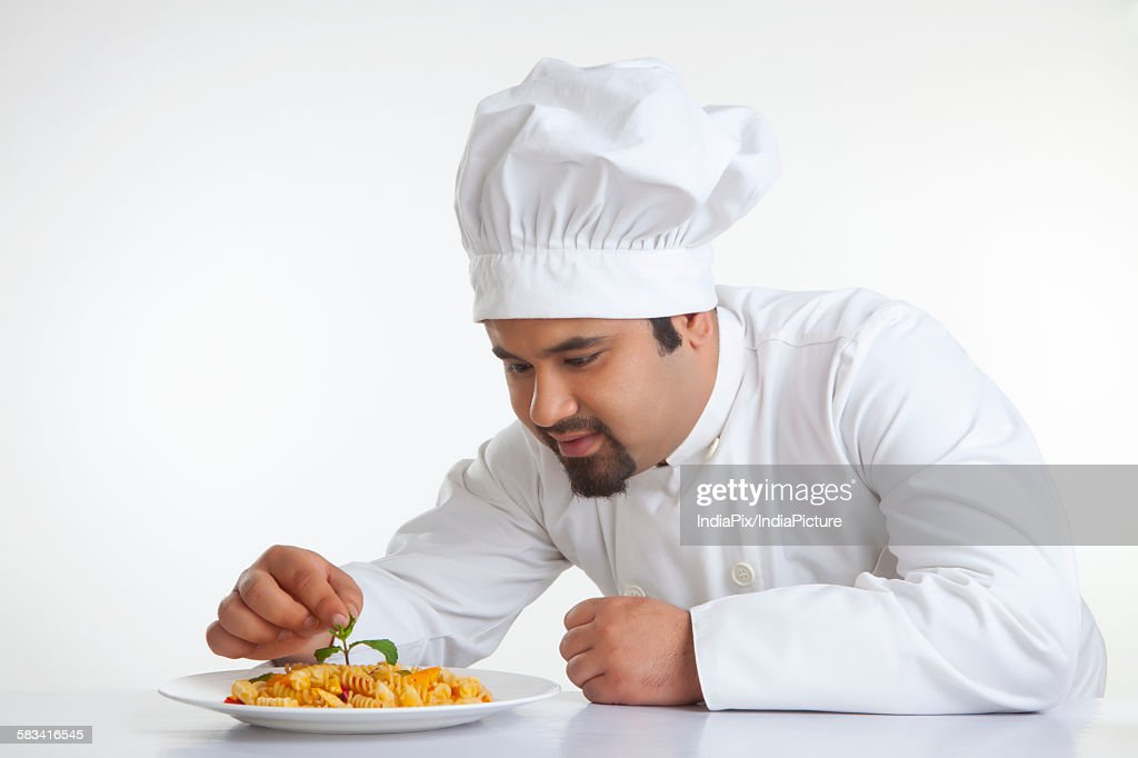 Chef decorating pasta with leaf : Stock Photo