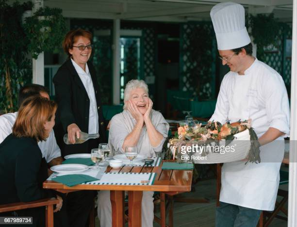 A chef delivers a fresh dish of seafood for French actress and singer Line Renaud and her guests while dining at a restaurant of the Royal Thalasso...