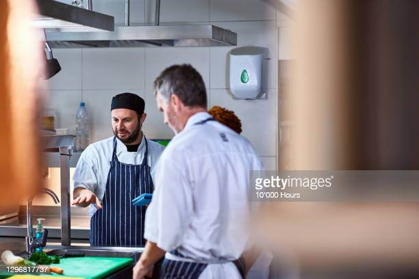 chef discussing with team in commercial kitchen - real people stock pictures, royalty-free photos & images