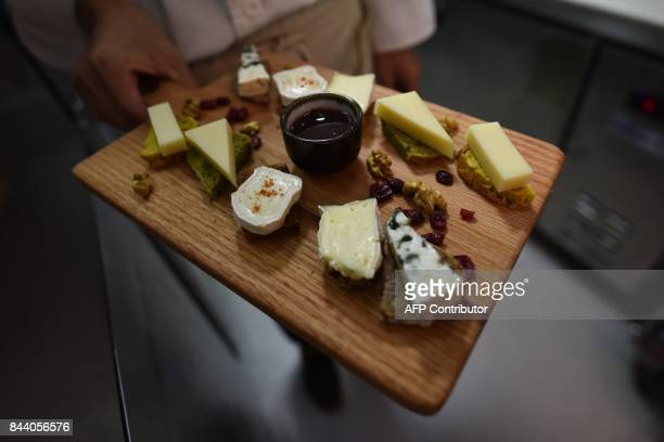 A chef displays a cheese platter featuring French brie and other cheeses at a restaurant in Beijing on September 8 2017 Camembert Brie and Roquefort...